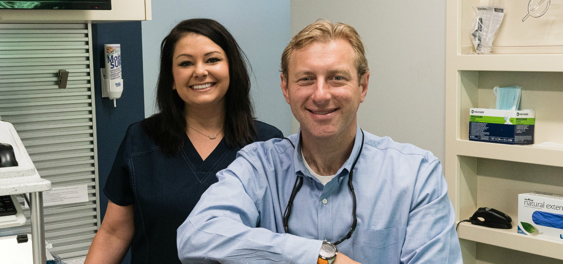 Dr. Bill and staff member smiling in a patient room at Durham DDS.