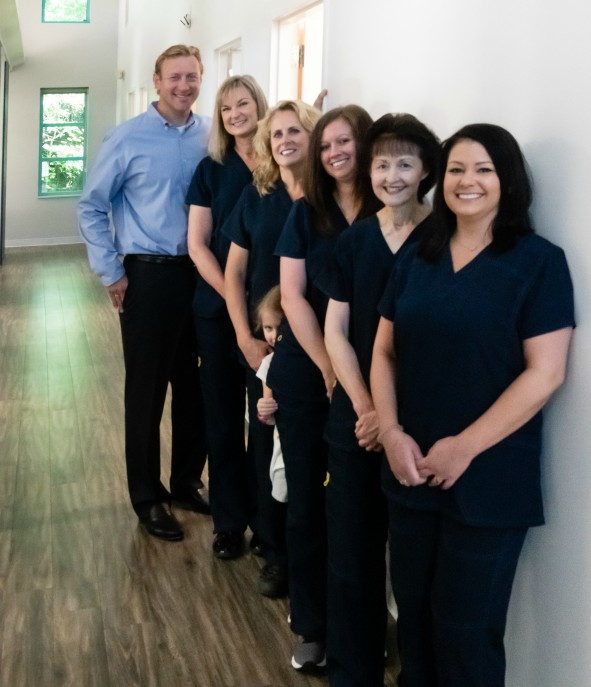 Staff of Durham DDS standing in a row inside the office.
